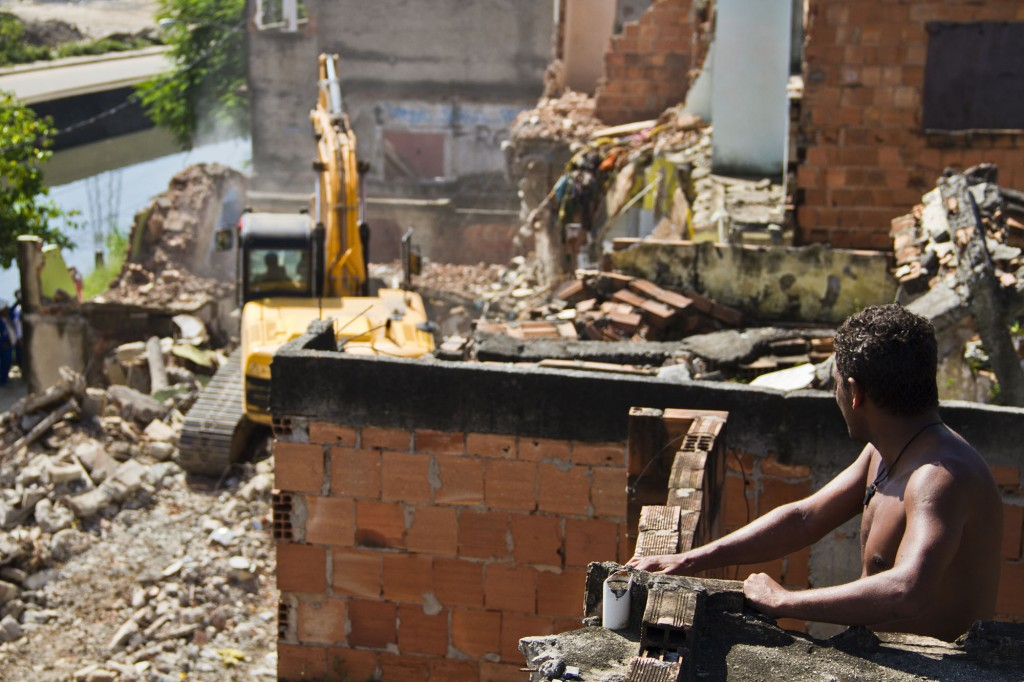 A resident looks on as a neighbor's home is demolished. Photo by AF Rodrigues