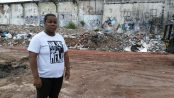 Resident Camila Santos stands in front of the remains of Favela da Skol.