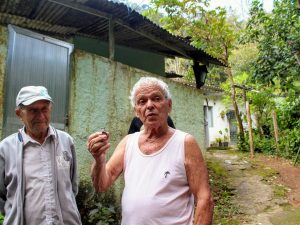 Seu Zeca holds his grandfather's whistle, who was one of the old guards of the Botanical Gardens.
