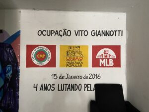The entrance of the Vito Giannotti occupation with the symbols of the social movements fighting for housing and responsible for its organization